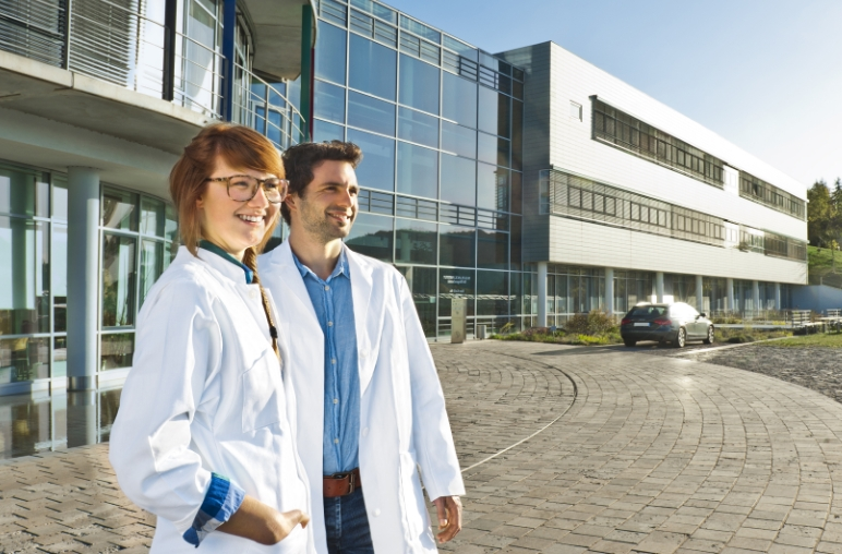 A man and a woman in lab coats stand in front of a modern building with a glass façade and look into the distance.