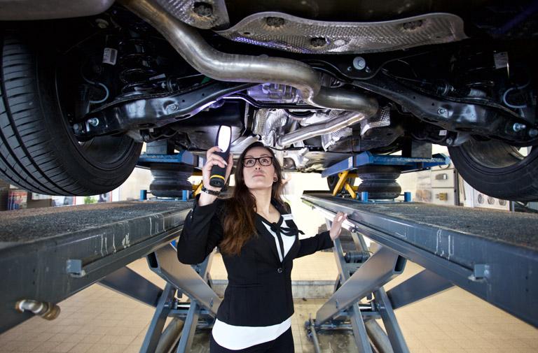 KFZ-Mechanikerin schraubt an Auto auf Hebebühne