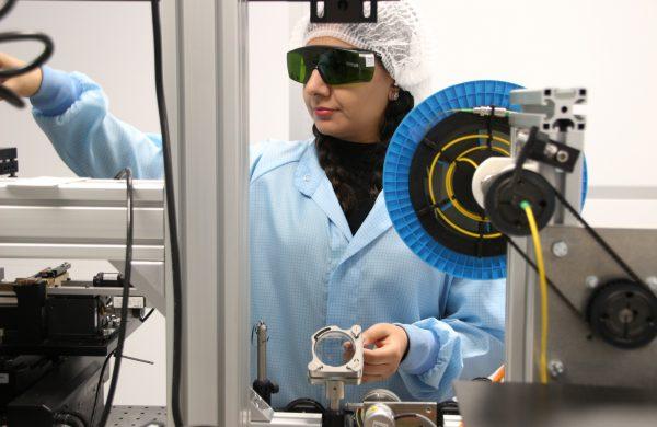 Eine Frau arbeitet in einem Reinraum und trägt Schutzkleidung.