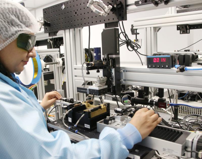 Eine Frau steht arbeitet in einem Reinraum an technischen Instrumenten und trägt dabei Schutzkleidung.