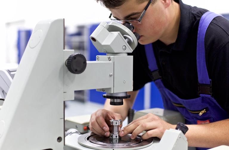 Junger Auszubildender schaut durch Mikroskop