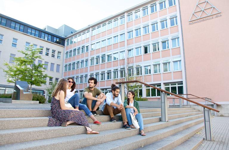 Fünf Studierende sitzen auf Treppe und sprechen