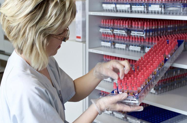 Frau hält kasten mit Ampullen in der Hand