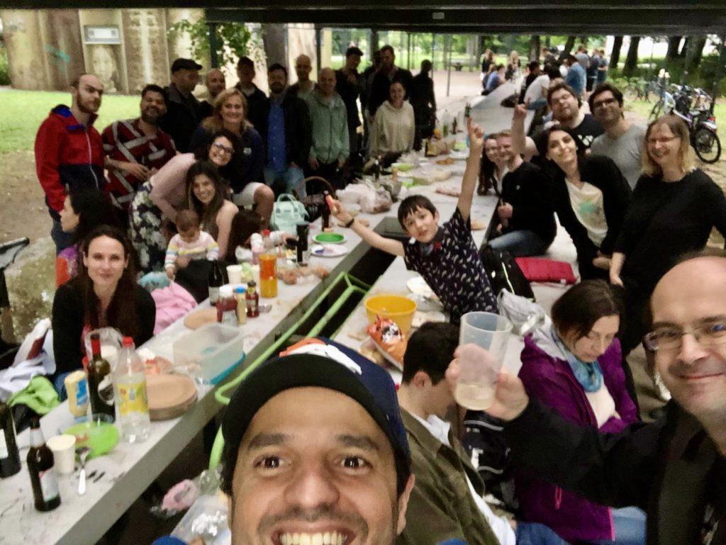 Gruppenselfie von Menschen, die gemeinsam an einer großen Tafel im Park sitzen und essen.