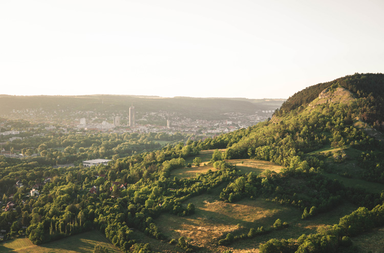 Blick aus der Höhe über Landschaft, bewachsene Hügel im Vordergrund,Skyline von Stadt im Hintergrund