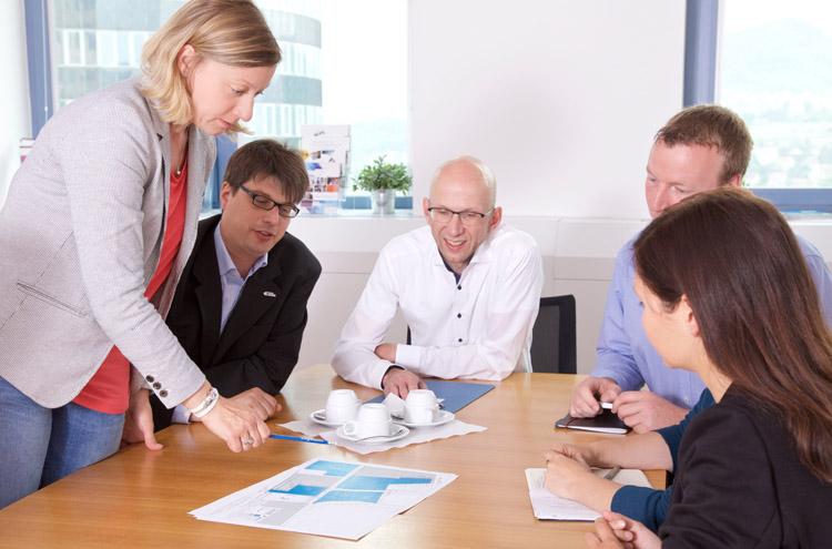 Gruppe von 6 Personen sitzt um Tisch und blicken auf Dokument in Tischmitte