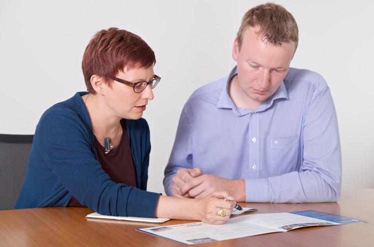 Frau und Mann sitzen an Tisch, blicken auf Dokument
