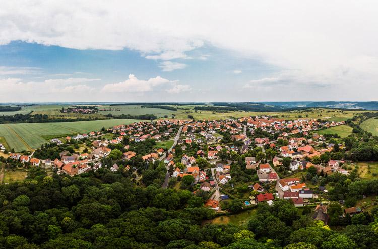 Blick aus der Höhe über zahlrecihe Einfamilienhäuser mit Natur und Wald drum herum