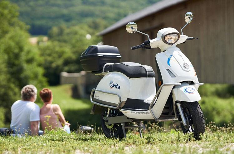 Elektro-Motorrad steht auf Wiese, im Hintergrund sitzt Pärchen unscharf