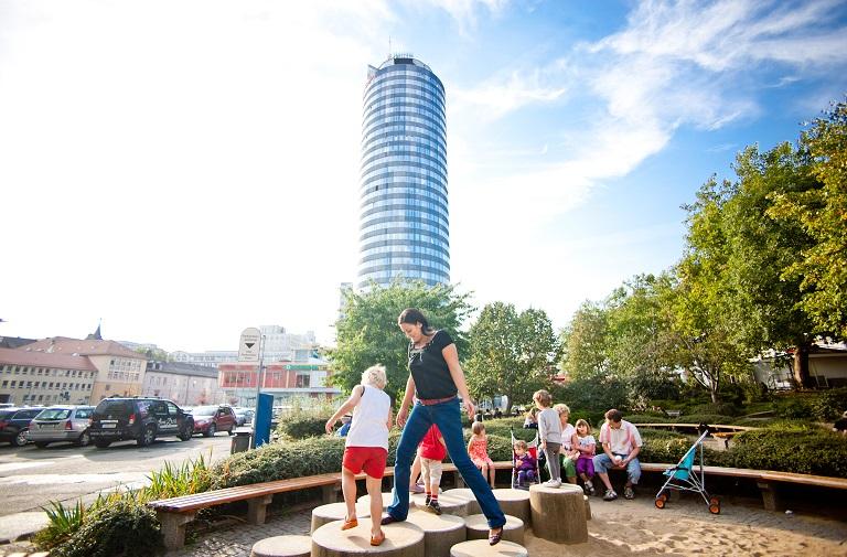 Familien auch kleinem Spielplatz in Innenstadt, Turm und Parkplatz im Hintergrund