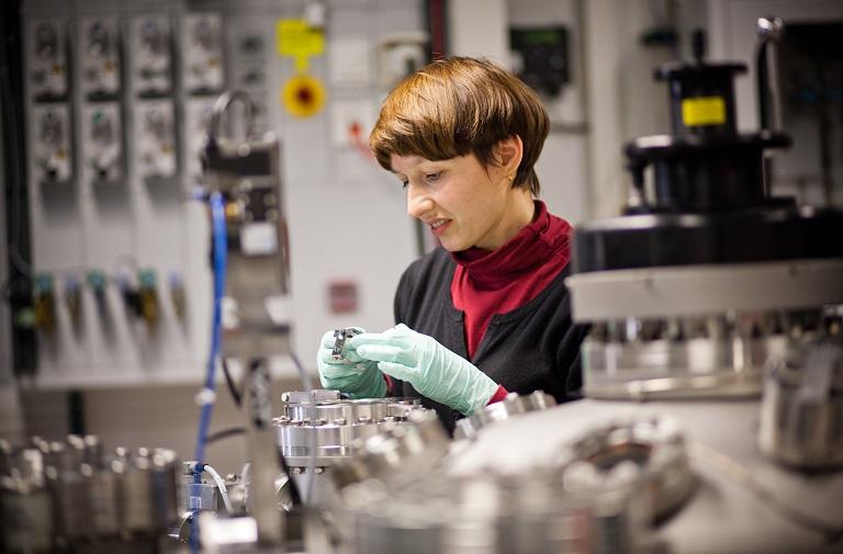 Forscherin untersucht Metallteil