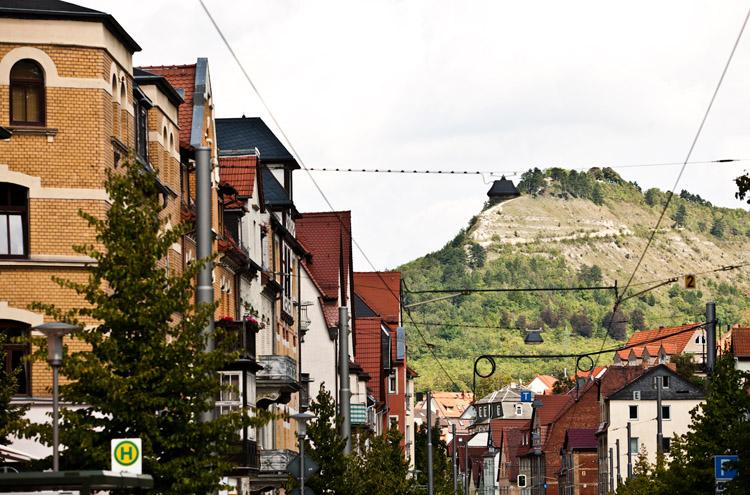 Blick zwischen 2 Häuserreihen, Berg im Hintergund mit grünem Hang
