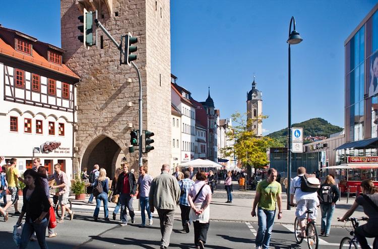 belebte Straßenkreuzung, zahlreiche Menschen überqueren Straße, im Hintergrund Gebäude, u.a. Kirchenturm