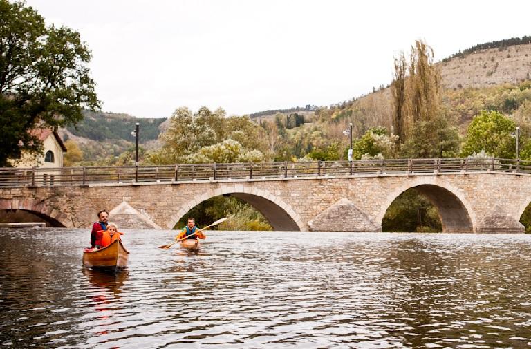 Familie in 2 Kanus fahren über Fluss, Brücke und Berge im Hintergrund