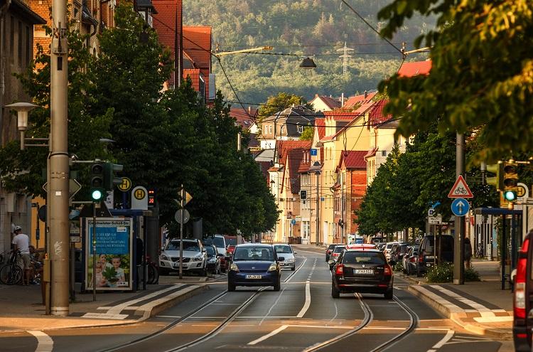 Straße, auf der Autos fahren, links und rechts Wohnhäuser