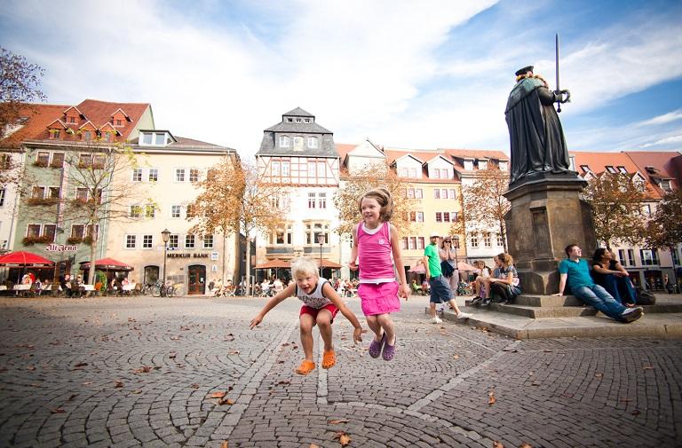 Kinder springen im Vordergrund, im Hintergrund Gebäude