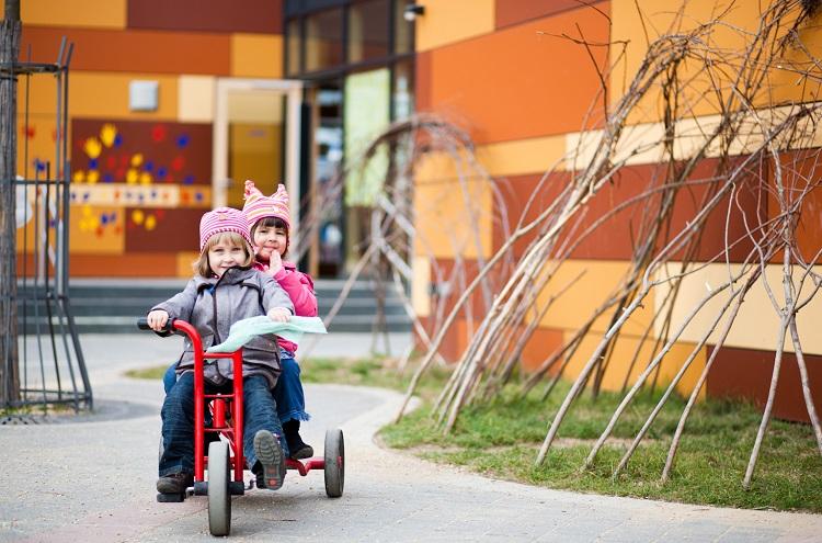 zwei Mädchen auf einem Zweisitzer-Dreirad vor dem Gebäude des Kindergartens