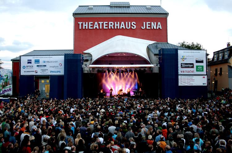 Konzert auf Bühne an Haus im Hintergrund, zahreiche Personen im Vordergrund