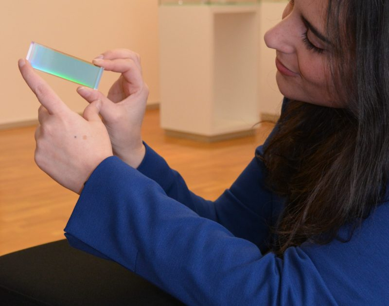 Eine Frau mit dunklen Haaren präsentiert eine Optik.