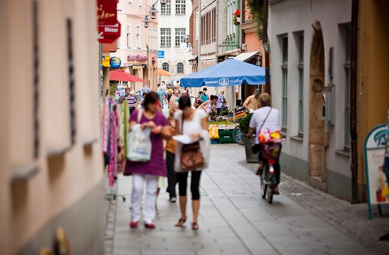 Einkaufsgasse mit zahlreichen Menschen, 2 Frauen unscharf im Vordergrund