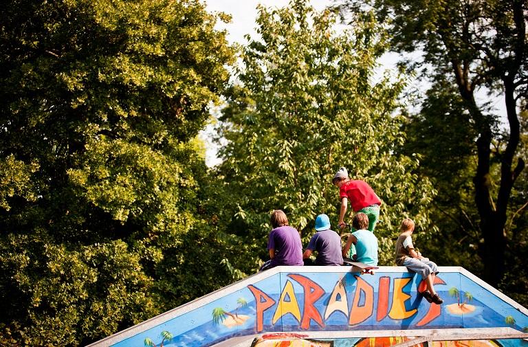 5 Jugendliche sitzen auf Half Pipe im Skate Park
