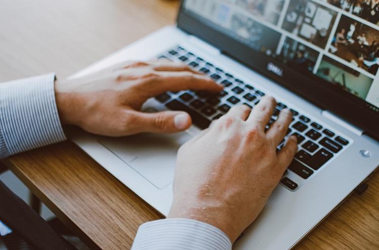 Person am Laptop, Nahaufnahme der Hände auf Tastatur