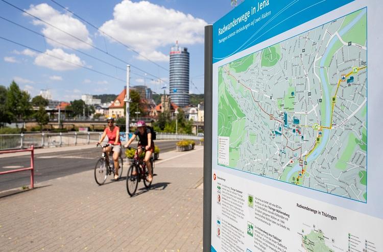 links Radfahrer unscharf, rechts Nahaufnahme von Stadtplan, Hintergrund Gebäude