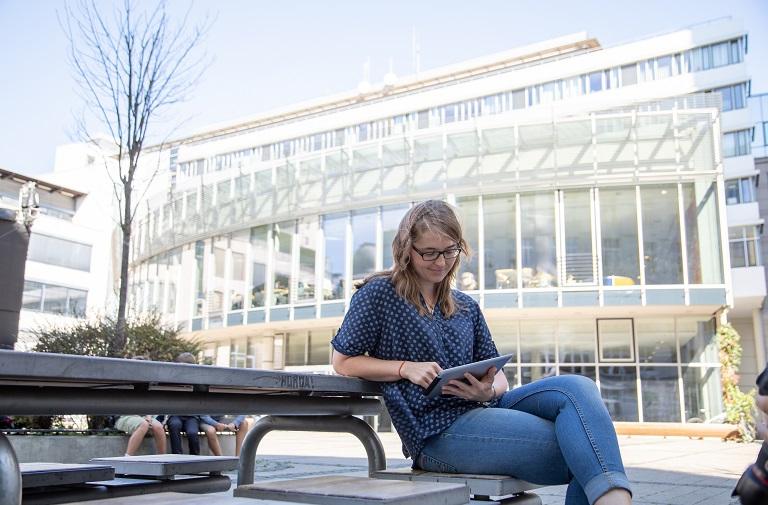 Studentin auf Unicampus sitzt auf Bank und liest auf Tablet