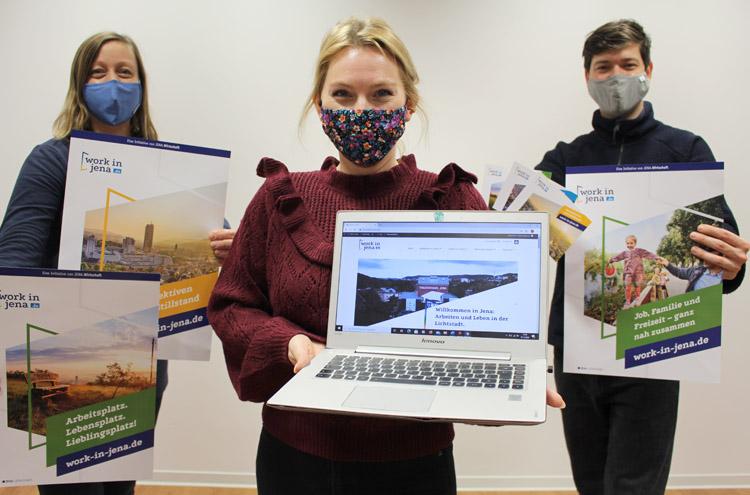 3 Personen mit Mund-Nasen-Bedeckung stehen nebeneinander, halten Plakate und Laptop in Kamera
