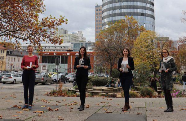4 Frauen stehen nebeneinander auf großem Platz, halten Buchstaben in der Hand, im Hintergund Gebäude und Parkplatz