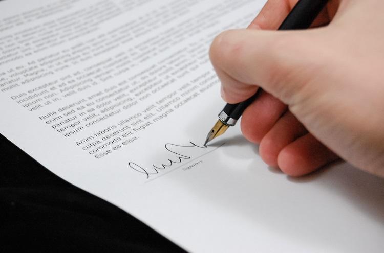 Nahaufnahme von Hand, die Stift hält und Dokument unterschreibt