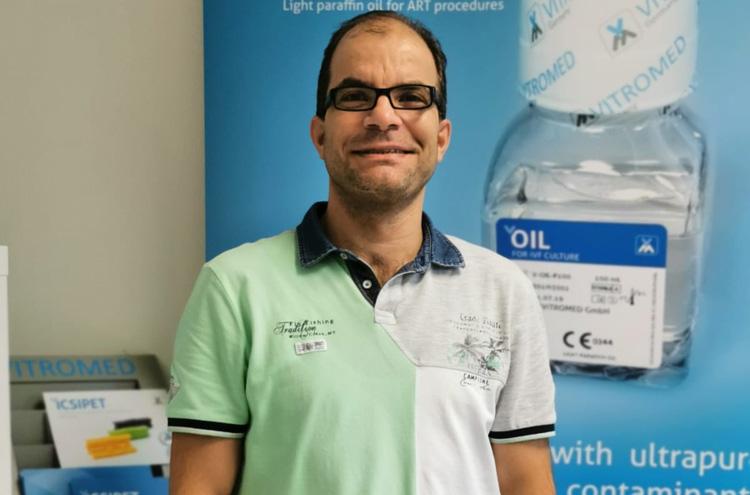 Mann mit Brille und dunklenb Haaren schaut Betrachter direkt am, im Hintergund Werbeplakate