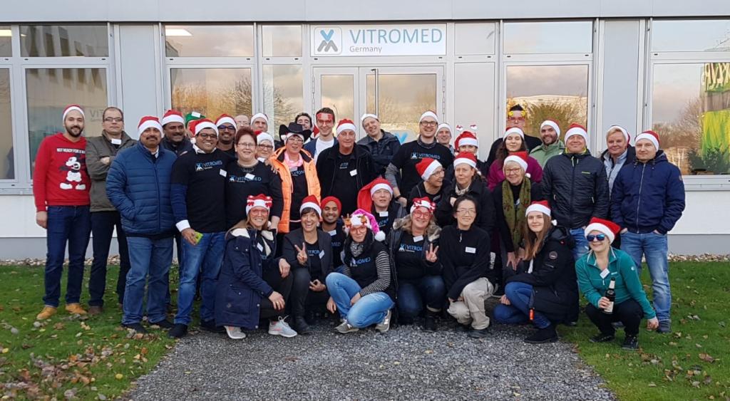 Gruppenfoto vor der Firma VITROMED. Die Personen tragen Weihnachtsmützen und sind gut gelaunt.