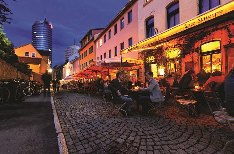 Blick in Jenas Wagnergasse bei Nacht, Menschen sitzen vor Lokalen und trinken und sprechen, Hintergrund Turm