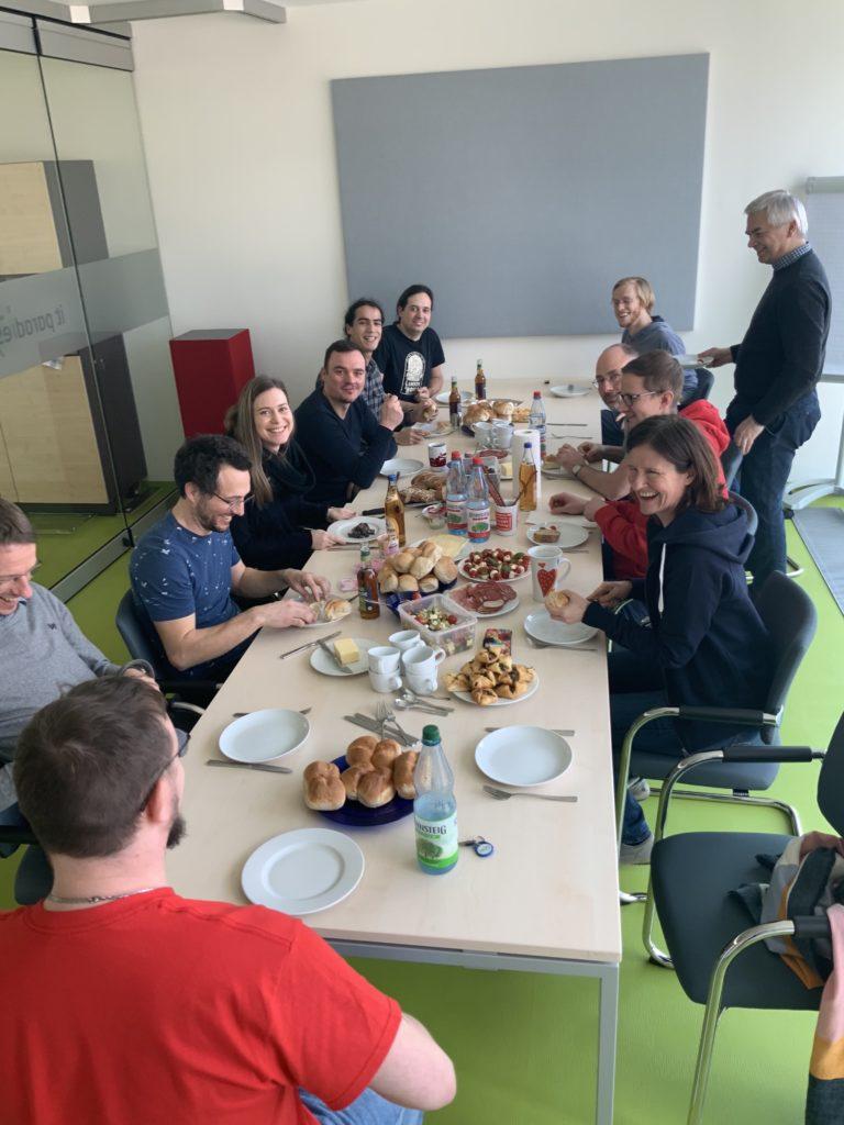 Zwölf Männer und Frauen sitzen um einen großen Tisch und essen zusammen. Auf dem Tisch stehen mehrere Teller mit vielen kleinen Speisen.