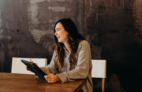 lächelnde Frau sitzt an Tisch mit Tablet in der Hand