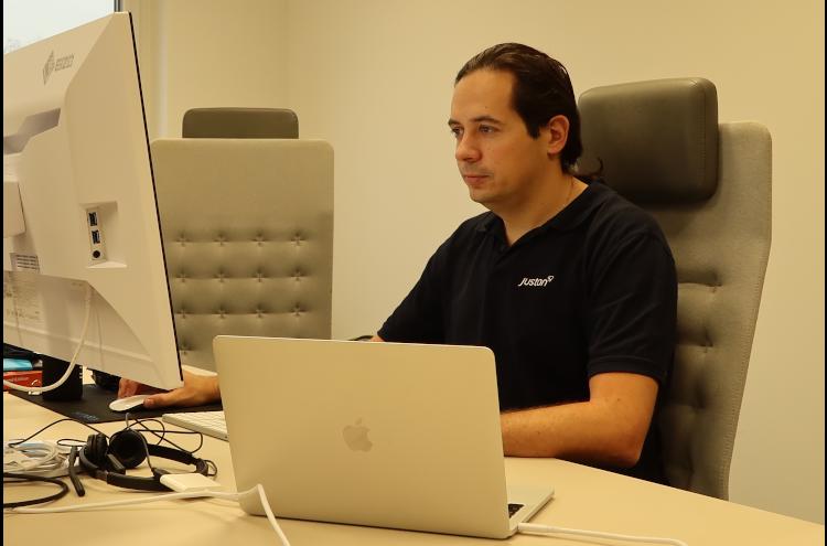 Ein Mann, der ein schwarzes T-Shirt trägt, sitzt an einem Schreibtisch und arbeitet an einem Computer.