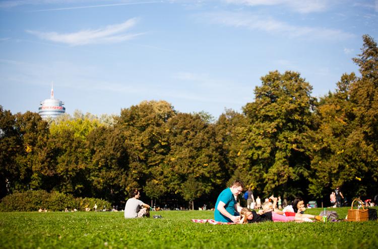 Menschen sitzen auf Wiese, im Hintergrund Bäume, dahinter Turm
