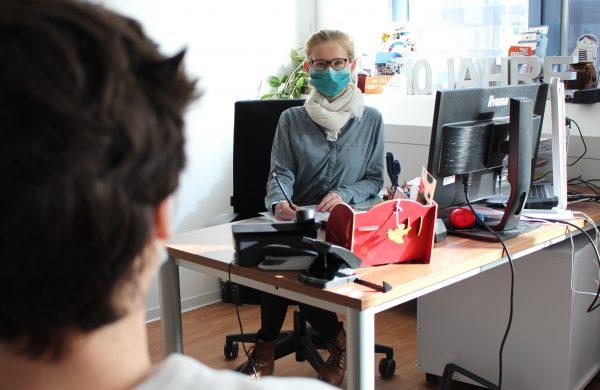 Eine Frau sitzt an einem Schreibtisch und berät eine zweite, männliche Person, die der Kamera den Rücken zugewendet hat.