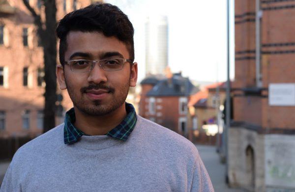 junger Mann mit schwarzen Haaren, Brille, Oberlippenbart, im Hintergrund die Skyline der Stadt