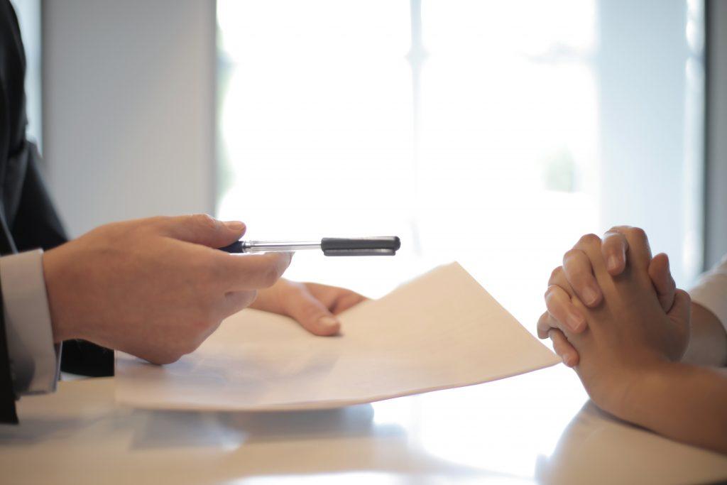 Das Bild zeigt die Hände eines Mannes und die Hände einer Frau. Der Mann hält in der linken Hand ein Blatt aus Papier und in der Rechten Hand einen Kugelschreiber.