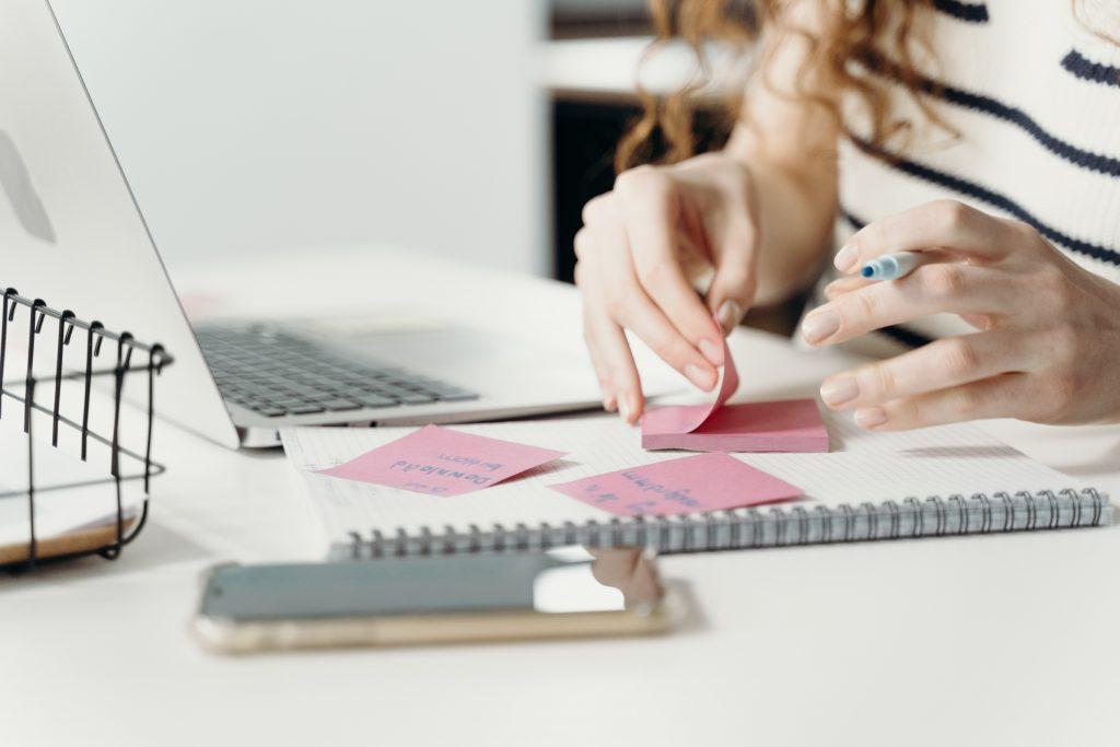 Das Bild zeigt die Hände einer Frau, die an einem Arbeitsplatz mit Zettel und Stift arbeitet.