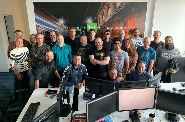 Gruppe von etwa 20 Menschen stehen eng zusammen und lächeln in Kamera, im Vordergrung PCs und Bildschirme
