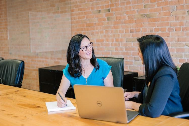 zwei Frauen im Gespräch am Beratungstisch, im Vordergrund ein Laptop