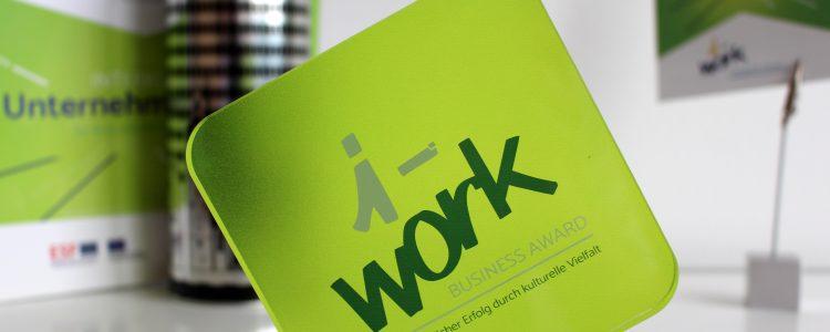 Nahaufnahme des i-work Business Award. Im Hintergrund Marketingmaterialien.